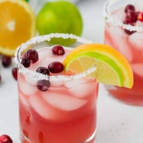 Image of a beautiful cranberry margarita in a salt rimmed glass, garnished with a lime wedge, an orange wedge, and fresh cranberries.