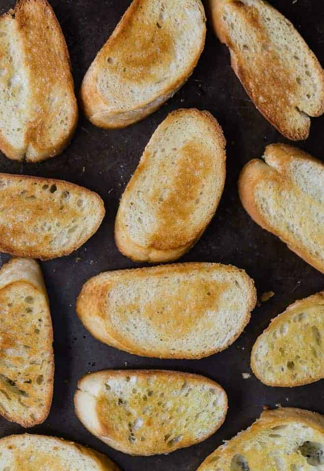 Photograph of crostini baked on a sheet pan.