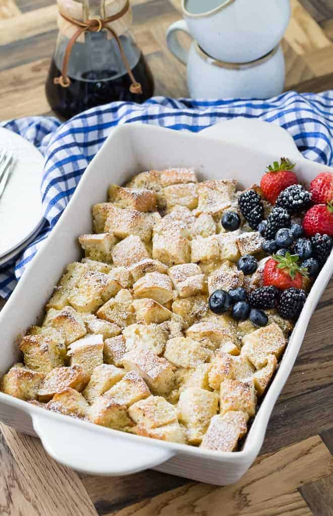 Image of overnight french toast casserole in a square baking dish, topped with powdered sugar and fresh berries.
