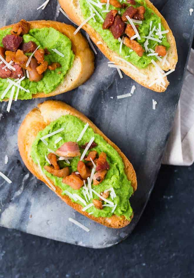 Image of creamy pea puree crostini, topped with crispy pancetta and vibrant white parmesan cheese.