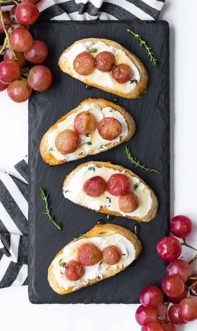 Image of four crostini on a small black slate board. Crostini is topped with roasted grapes and ricotta cheese.