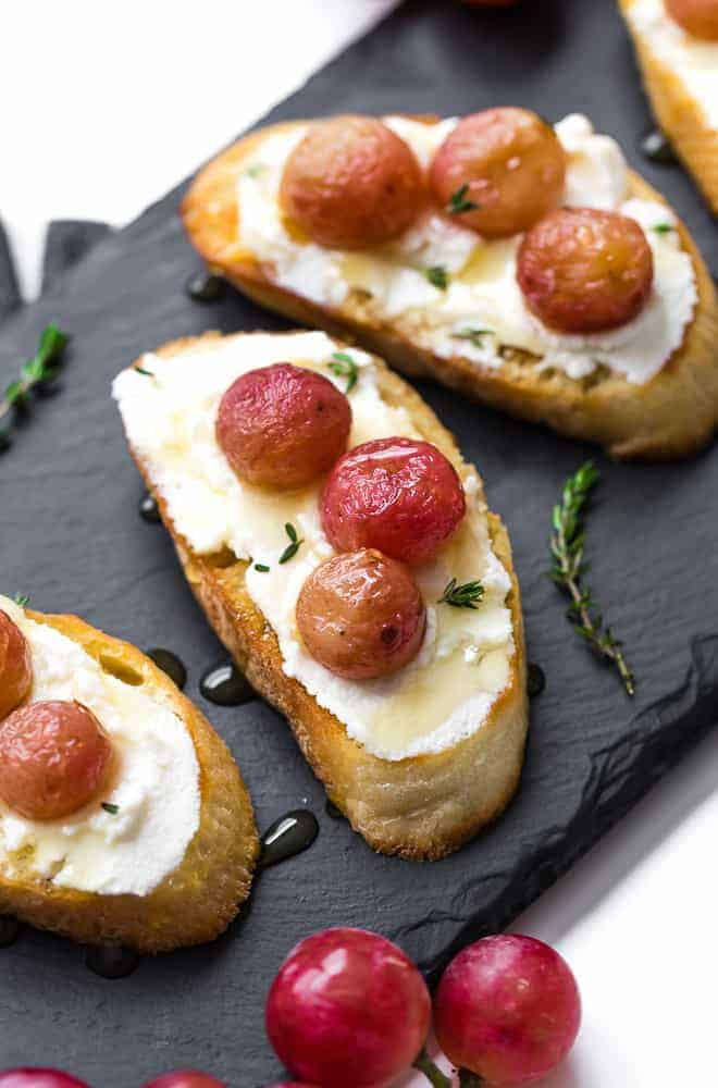 Image of crostini on a black slate board. It is stopped with ricotta cheese, roasted grapes, honey, and thyme.