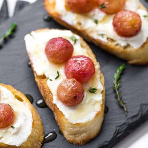 Image of roasted grape crostini on a black slate board, topped with ricotta, roasted grapes, and a drizzle of honey.
