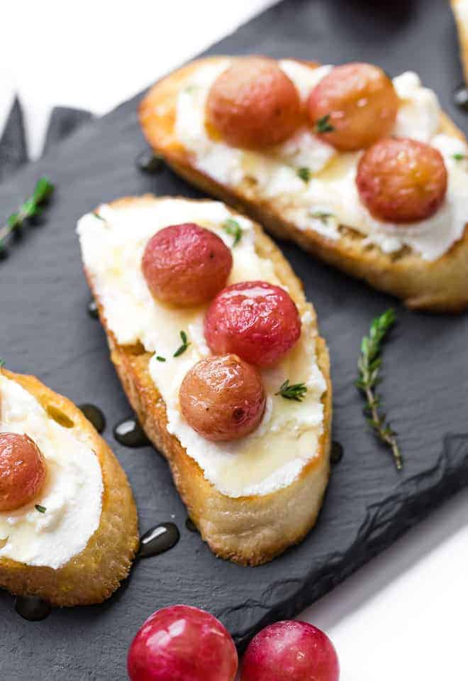 Image of crostini on a black slate background. They are topped with ricotta cheese, honey, and roasted grapes.