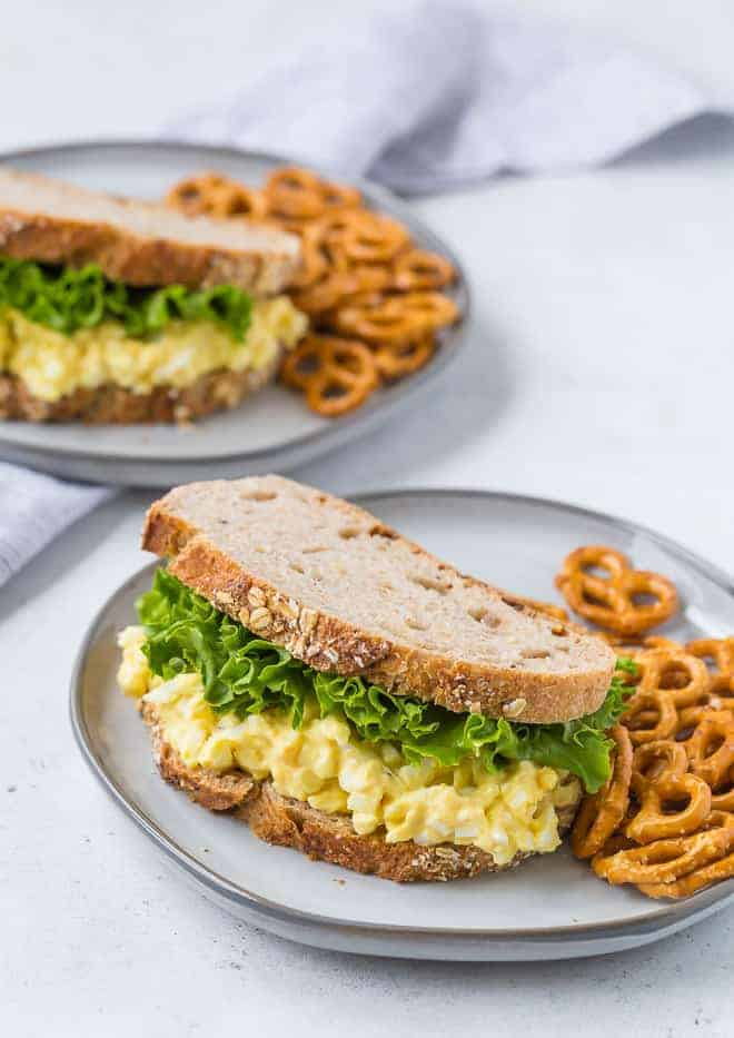 Image of egg salad on wheat bread with leaf lettuce. Pretzels are also on the plate.