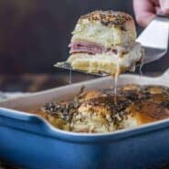 Image of ham and cheese sliders being taken out of a pan.