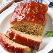 Image of moist meatloaf with a shiny tomato glaze, cut into slices.