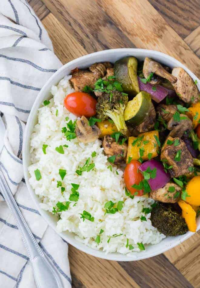 Image of sheet pan honey balsamic chicken and vegetables (tomatoes, peppers, broccoli, onions, mushrooms), served with rice and garnished with parsley.