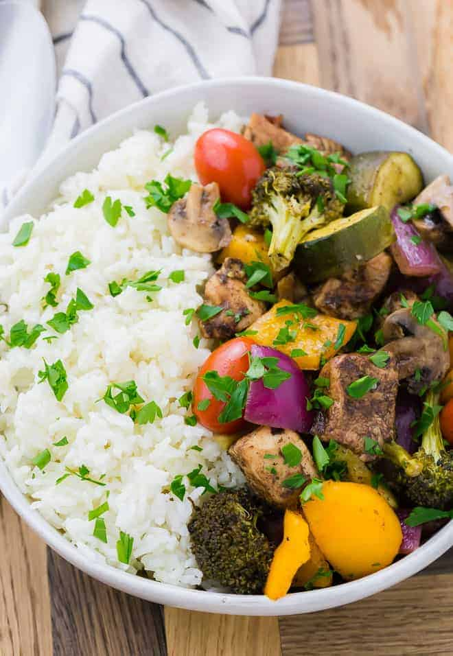 Image of a bowl of rice, chicken, mushrooms, peppers, onions, zucchini, broccoli, and tomatoes. This meal is garnished with fresh parsley.