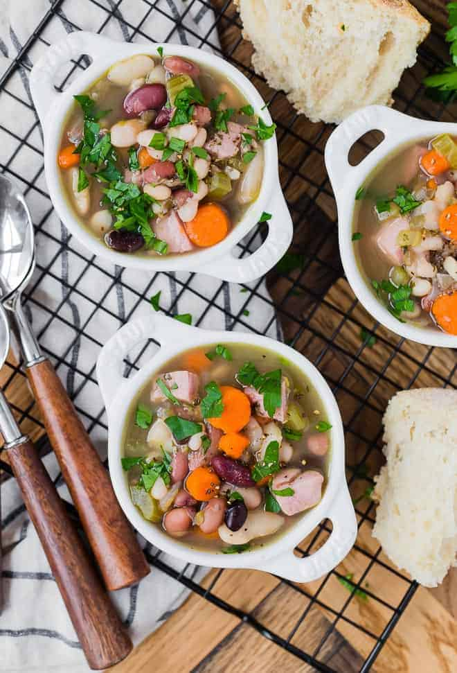Overhead image of three small bowls of bean and ham soup with bread and spoons also pictured.