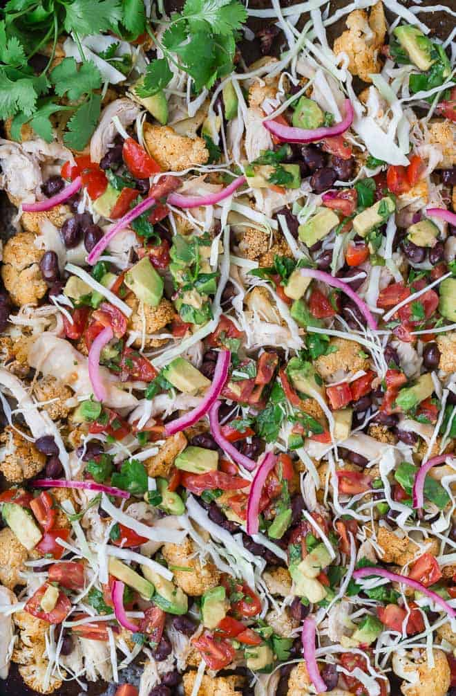 Image of the best cauliflower nachos topped with pickled red onions, shredded cabbage, and an easy avocado salsa.