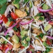 烤菜花的图片配上西南部风味的分类:腌制红洋葱,西红柿,白菜,鳄梨,黑豆和奶酪丝。
