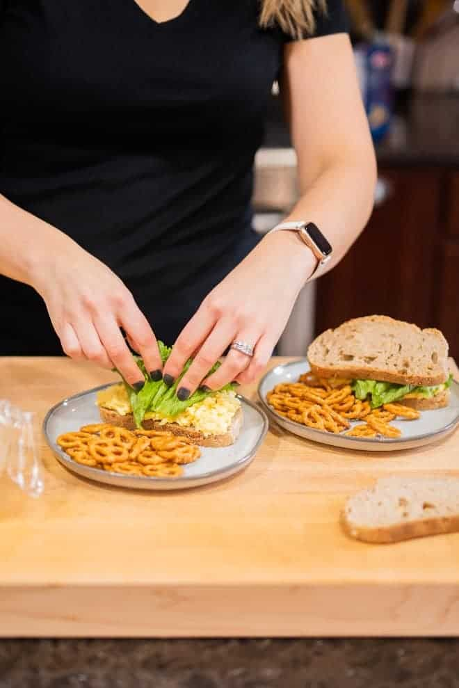 Image of Rachel Gurk putting together an egg salad sandwich, and pairing it with pretzels.