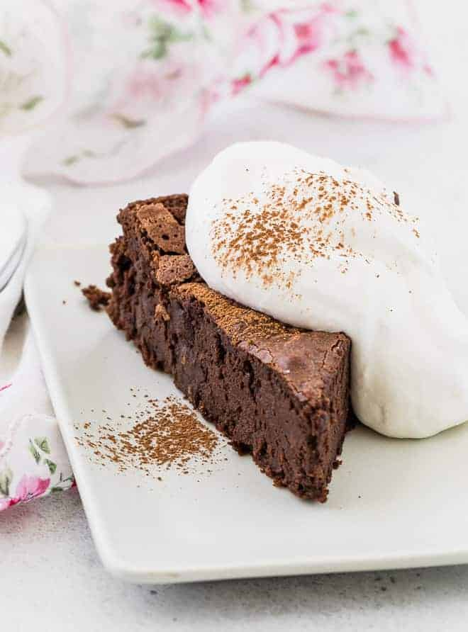 Image of chocolate chile cake sliced on a plate with whipped cream.