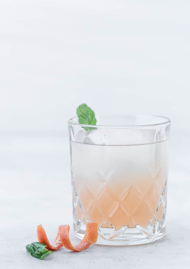 Image of a pink grapefruit cocktail made with gin and elderflower liqueur. The drink is garnished with a fresh basil leaf.