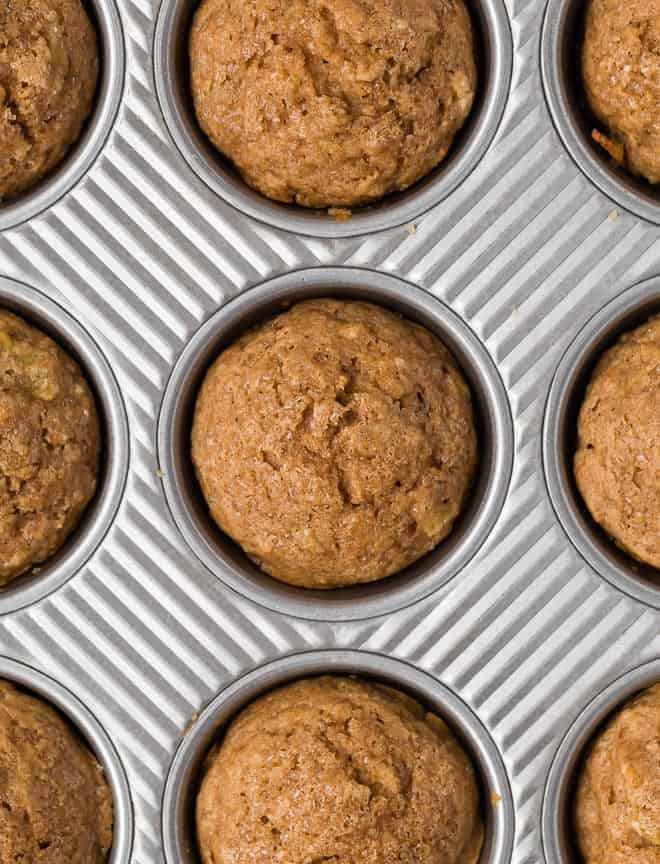 Overhead image of apple cinnamon muffins in a muffin tin.