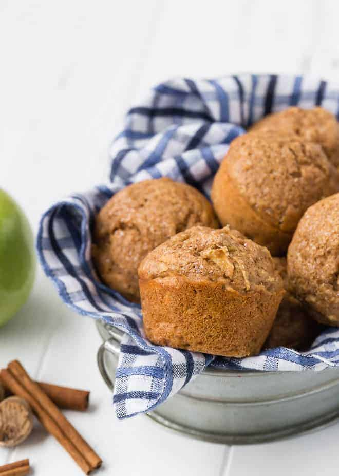 Image of whole wheat apple muffins in a metal basket with a blue and white checkered towel.