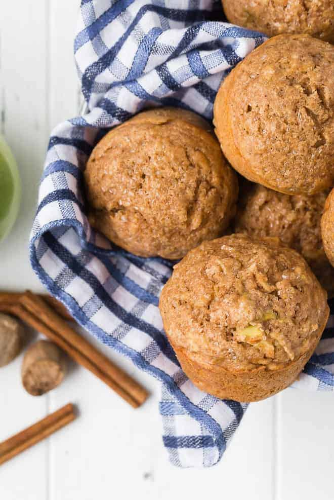 Image of healthy apple muffins in a basket with a blue checkered towel.