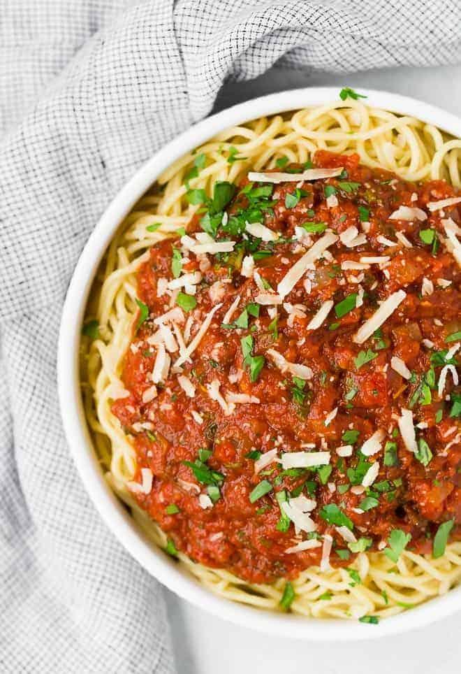意大利面条配自制酱汁的图片。这碗意大利面用帕尔马干酪和新鲜欧芹装饰。
