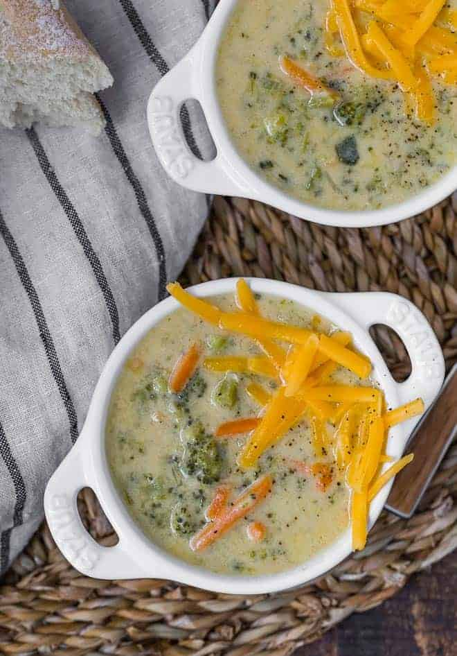 Image of two bowls of broccoli cheddar soup in white crocks with handles. Soup is garnished with additional cheddar cheese.