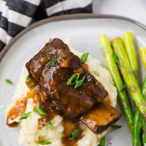 Image of a cooked short rib and gravy atop a pile of creamy mashed potatoes.