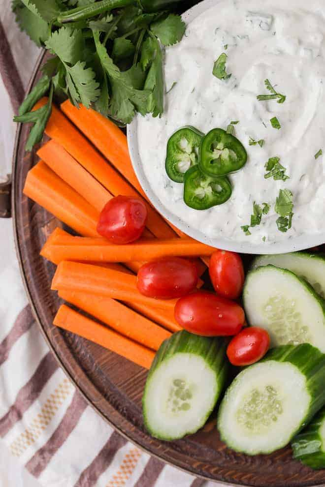 Image of creamy white vegetable dip garnished with jalapeno and surrounded with fresh vegetables on a wooden tray.