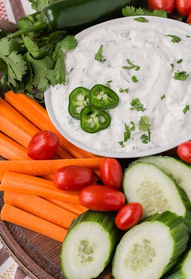 Image of jalapeño ranch dip on a vegetable platter, garnished with cilantro and additional jalapeño.