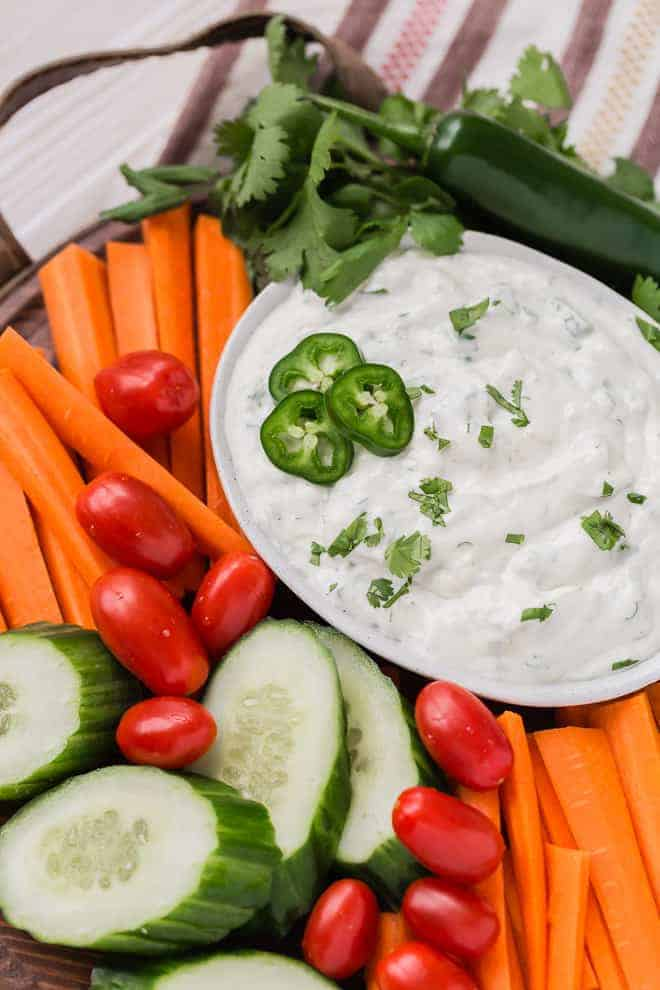 Image of spicy ranch dip in a bowl, surrounded by fresh carrots, tomatoes, and cucumbers.