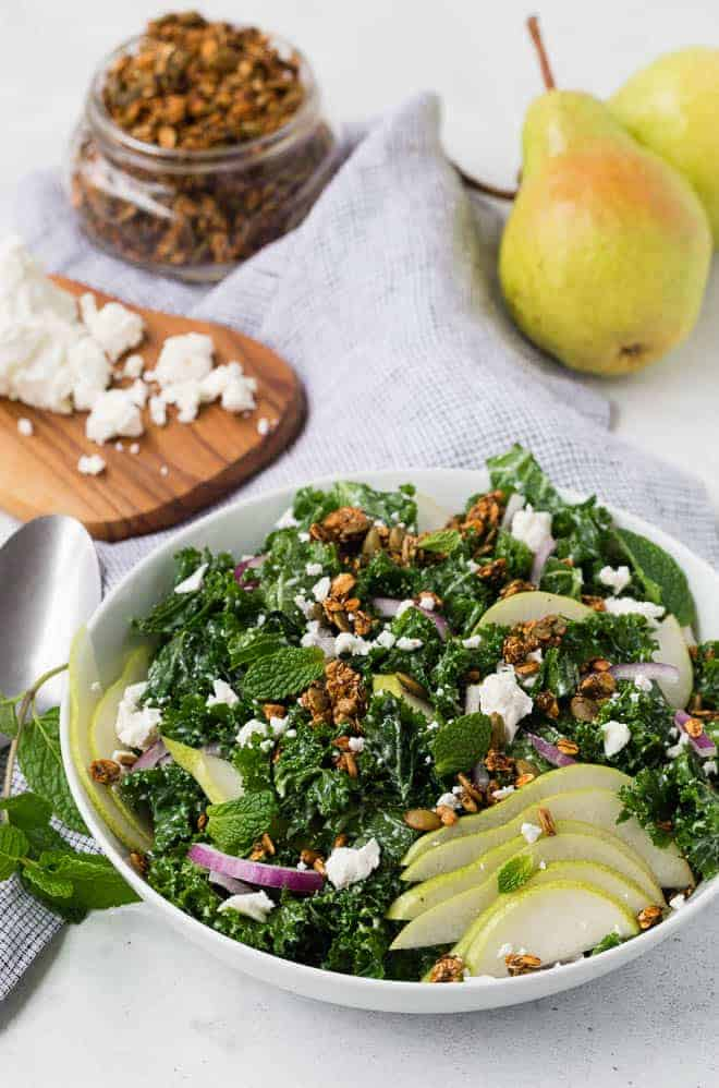 Kale salad topped with pear, feta, and savory granola.