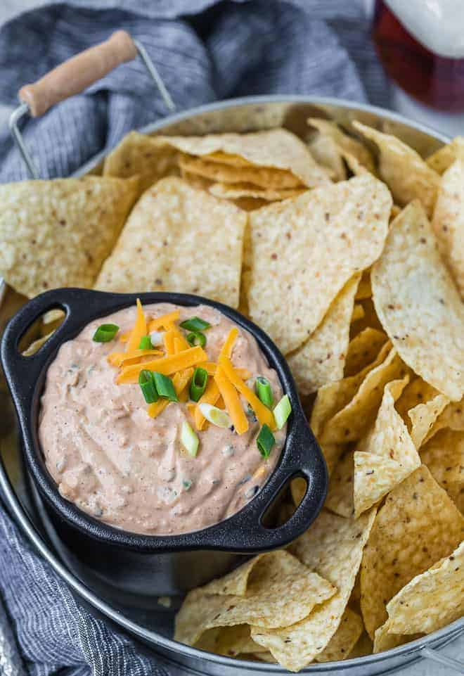 Image of mexican style creamy dip served on a tray with chips.