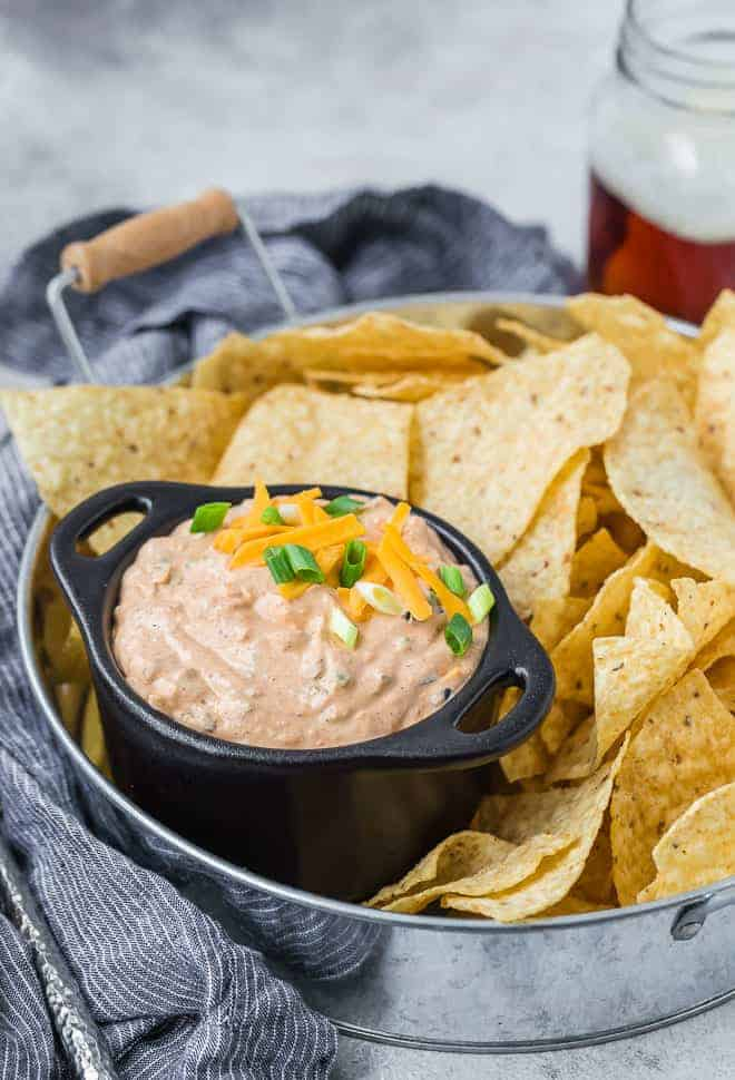 Image of creamy southwestern dip made with cream cheese, sour cream, mayo, green onions, jalapenos, olives, and cheddar cheese. Irresistible! Pictured served on a tray with chips.