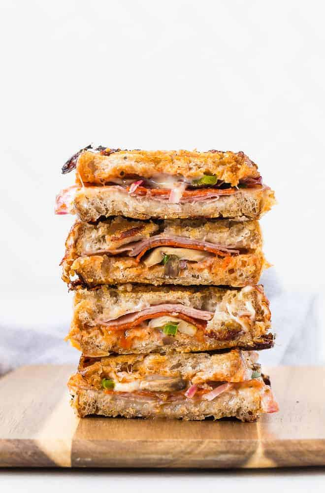 Stacked up pizza panini halves with pepperoni, pizza sauce, and vegetables.