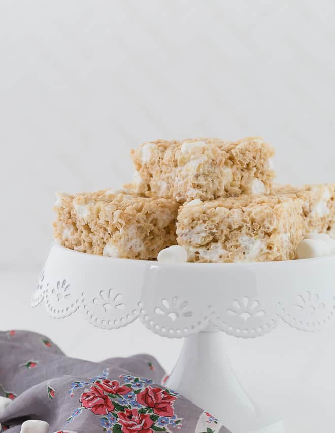 Image of the best rice krispies treats on a small white cake stand. Mini marshmallows are scattered around.