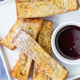 Image of a square white plate with 5 french toast sticks on it, sprinkled with powdered sugar. Also pictured is a small glass bowl of maple syrup.