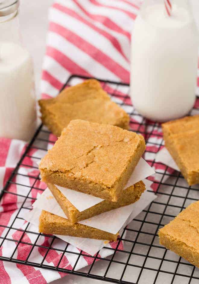 Easy to make blondie recipe creates the caramely blondies pictured in this image. They are stacked up with parchment paper separating them, with milk in the background.