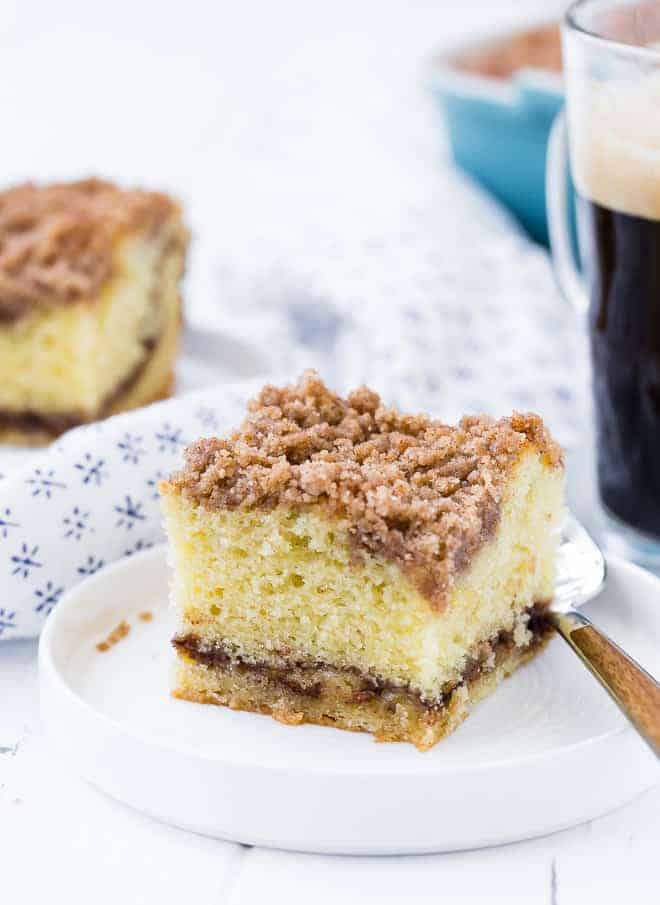 Image of a slice of coffee cake with streusel topping and cinnamon filling.