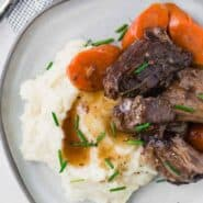 Image of pot roast piled on top of mashed potatoes. Carrots also pictured.