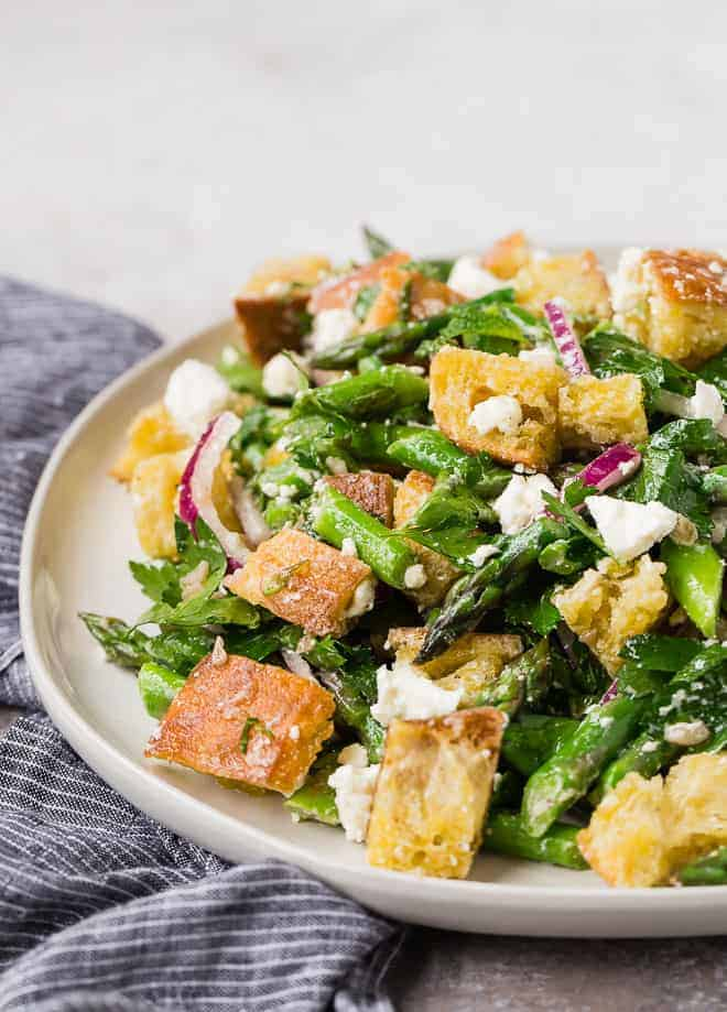 Image of a panzanella salad made with croutons, asparagus, mint, parsley, feta, red onion, and red wine vinaigrette.