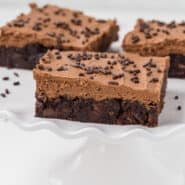 Image of mocha brownies with frosting, on a cake stand.