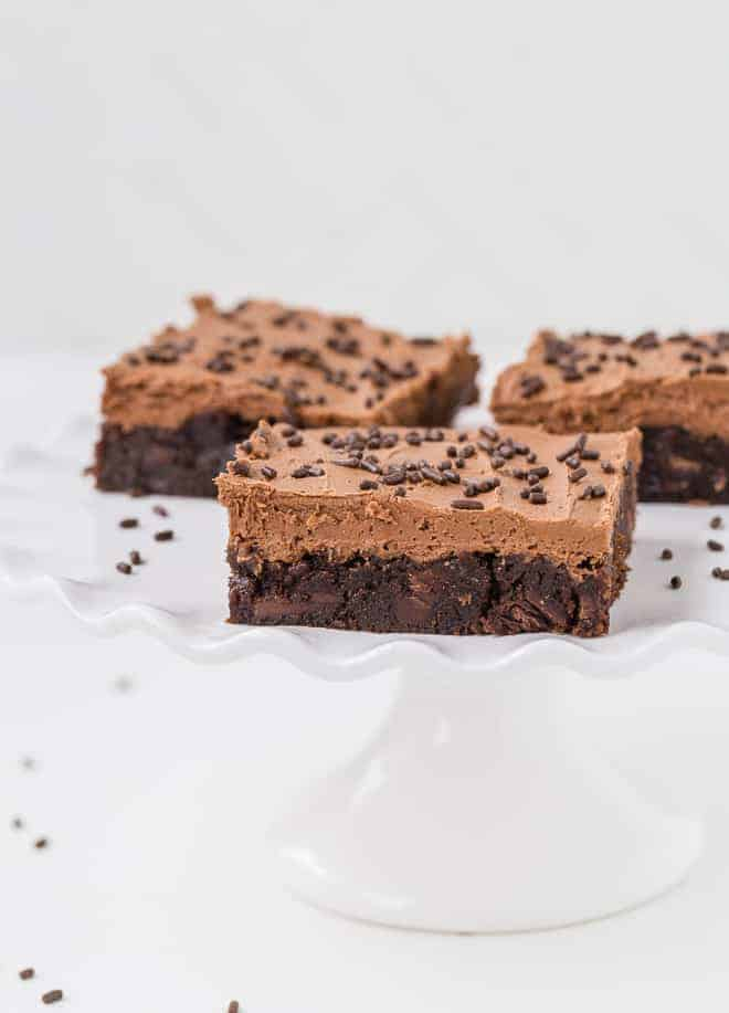 Image of mocha brownies on a ruffled white small cake stand. They are frosted and garnished with chocolate sprinkles.