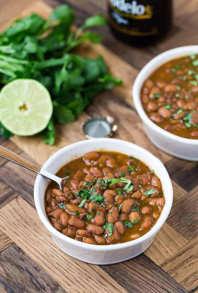Image of drunken beans in a white bowl with a spoon. A beer bottle cap, lime half, and fresh cilantro are in the background of the photo.