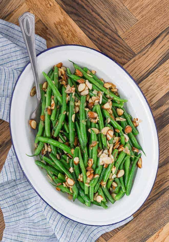 完美煮熟的形象,明亮的绿色的青豆在白色的盘子。它们与烤杏仁和新鲜柠檬皮一起烹调。