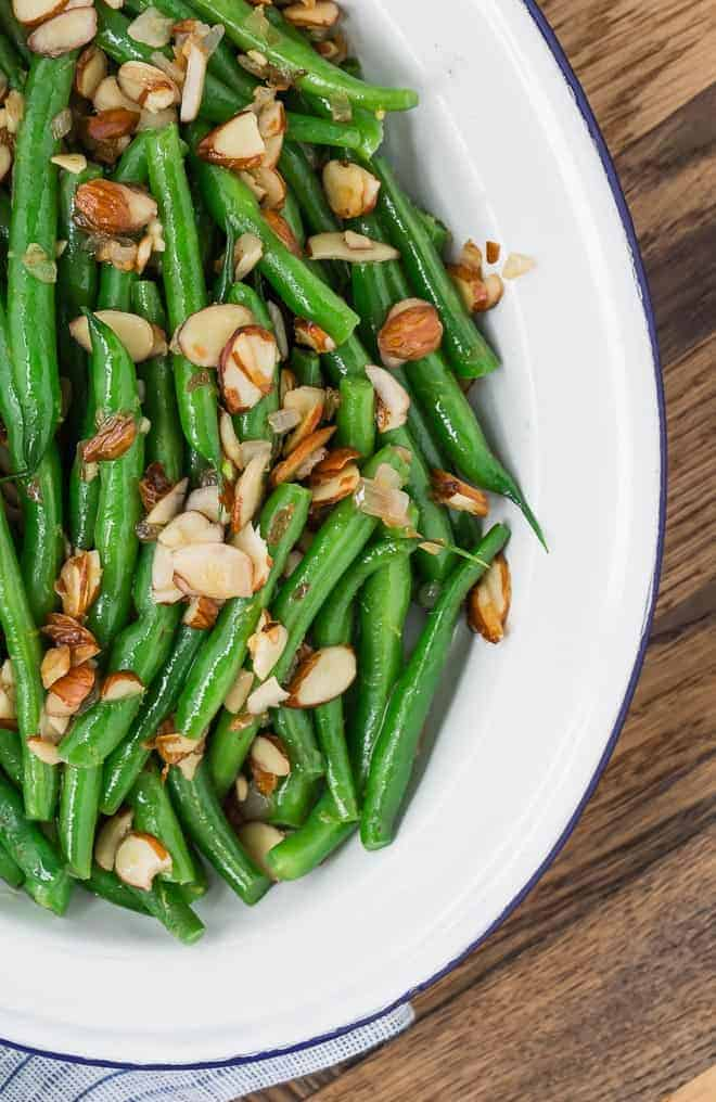 Image of green beans almondine, bright green and garnished with almonds and lemon zest.