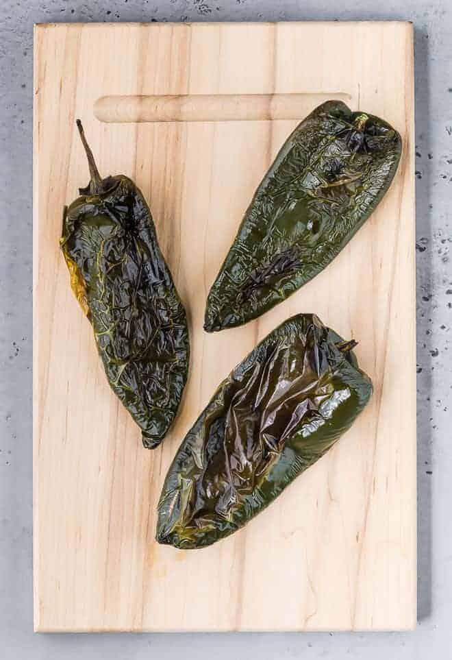 Image of roasted poblano peppers that haven't been peeled.
