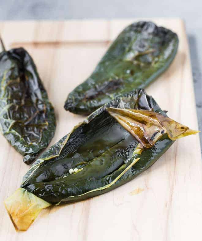 Image of roasted poblano peppers, peelings beginning to be removed.