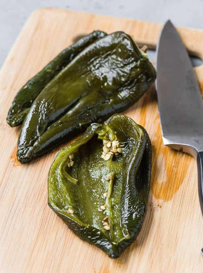 Image of roasted poblano peppers that have been peeled. One has been cut open to show the inside.