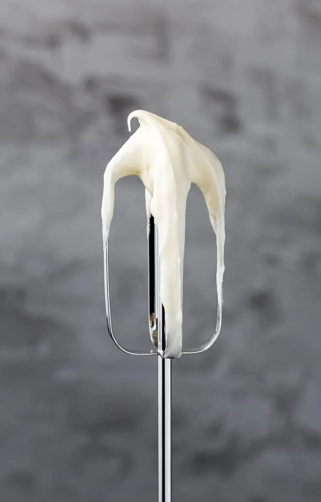 Image of an electric mixer beater with lemon cream cheese frosting on it.