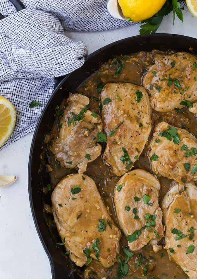 Image of pork tenderloin slices cooked in a lemon garlic sauce, in a black frying pan. Lemons, garlic and fresh parsley are sprinkled throughout the photo.,