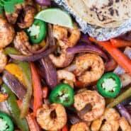 在片材上五颜六色虾法士达平移与玉米饼,酸橙,辣椒,和香菜。