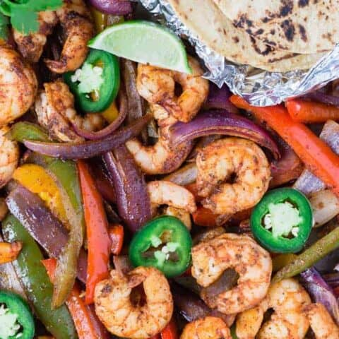 Colorful shrimp fajitas on a sheet pan with tortillas, limes, jalapeno, and cilantro.